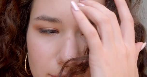 Closeup portré fiatal, hosszú hajú, göndör kaukázusi női modell mosolygó boldogan nézi kamera napsütésben az arcán a szél fúj