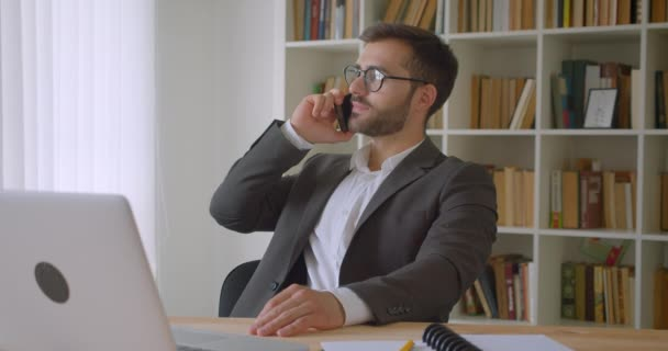Closeup portrait of adult handsome bearded caucasian businessman in glasses having a phone call sitting in front of the laptop in the office indoors with bookshelves on the background