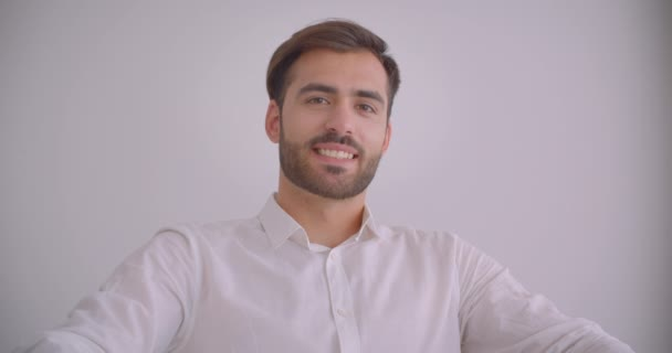 Pohled na portrét dospělého vousatého bělocha, který se vesele usmívá, sedí v křesle v bílé kanceláři