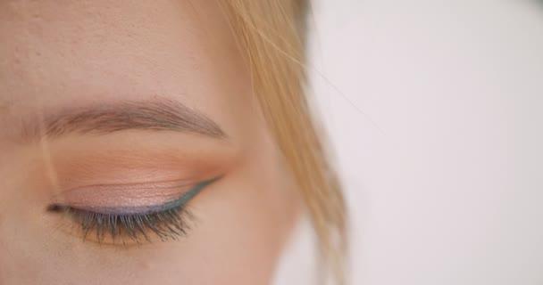 Closeup fél arcképe a fiatal szőke kaukázusi női arc szemmel nézett kamera háttérrel izolált fehér