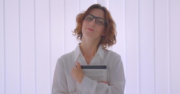 Zápisky na portrétu dospělé zrzavé ženy v brýlích s knihou s úsměvem usmívajícími se v bílém bytě
