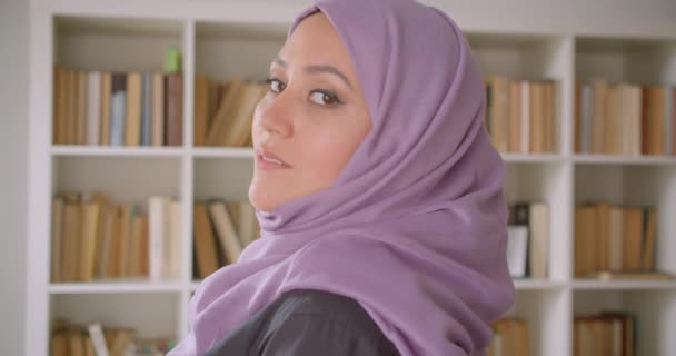 Closeup portrait of young pretty muslim female student in hijab turning and looking at camera in library