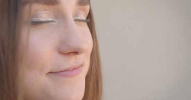 Closeup side view shoot of young pretty caucasian female face with hair rings and glitter makeup with eyes joyfully looking at camera in the white room indoors