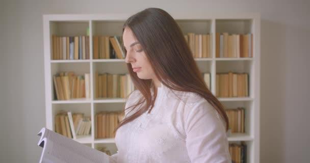Closeup portrét mladého bělošského studentky, který čte knihu a dívá se na kameru dovnitř v knihovně