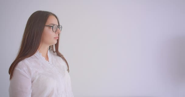 Closeup portrait of young pretty caucasian female in glasses looking at camera having her arms crossed over chest with background isolated on white