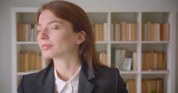 Closeup portrét mladé kavkazské ženy, která se dívala na kameru v knihovně