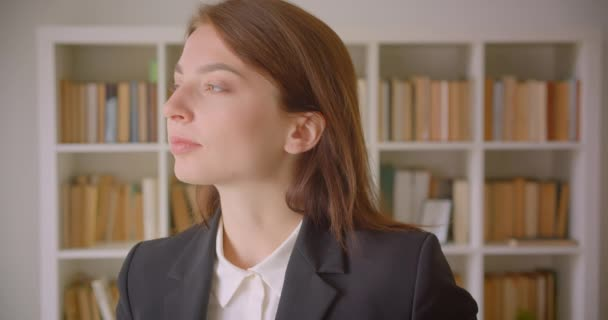 Closeup portrait of young caucasian businesswoman looking at camera smiling cheerfully in the library indoors with bookshelves on the background