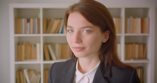 Closeup portrait of young caucasian businesswoman looking at camera smiling in the library indoors