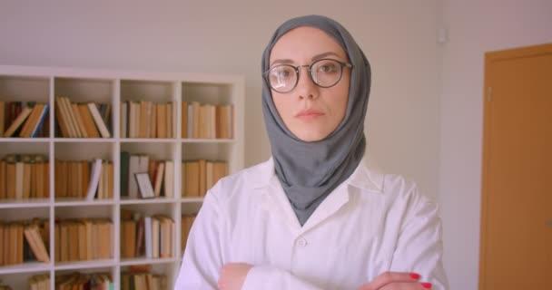 Nahaufnahme Porträt einer jungen muslimischen Ärztin mit Brille und Hijab, die mit verschränkten Armen in der Bibliothek drinnen in die Kamera blickt