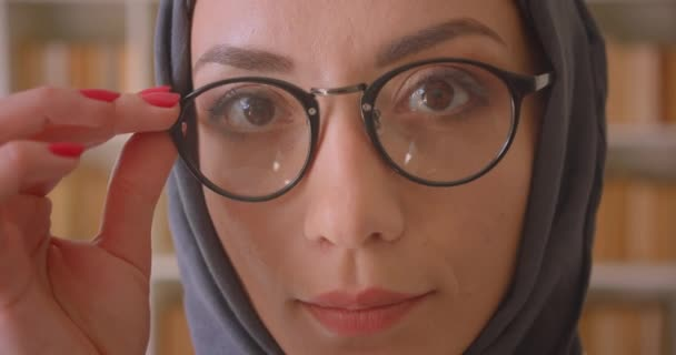 Closeup portré fiatal Arab női arc a szemüveg és hidzsáb nézi kamera mosolygó vidáman könyvtár beltéri