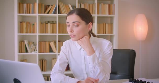 Closeup portrét mladé atraktivní kavkazské ženy používající notebook v kanceláři v interiéru s policemi na pozadí