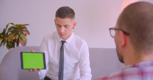 Closeup portrait of customer service manager talking to client showing tablet with green screen in office