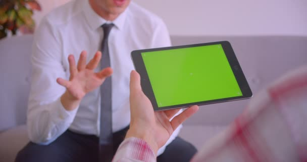Closeup portrait of customer service manager talking to client holding tablet with green chroma screen in office