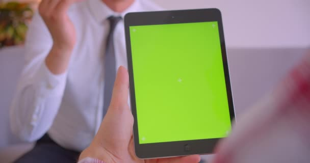 Closeup portrait of customer manager talking to client holding tablet with green chroma key screen in office