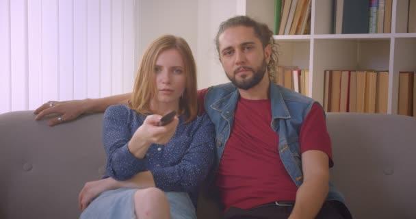 Csípő fiatal pár nézi vígjáték film a TV és a beszélő vidáman otthon.