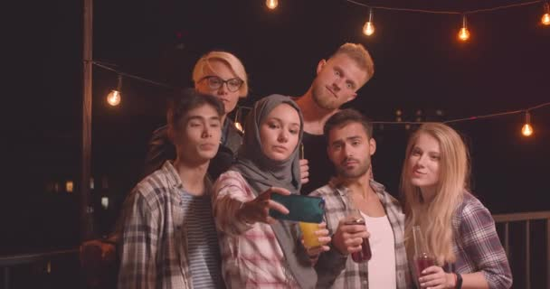 Closeup portrait of diverse multiracial group of friends taking selfies at fun party in cozy evening