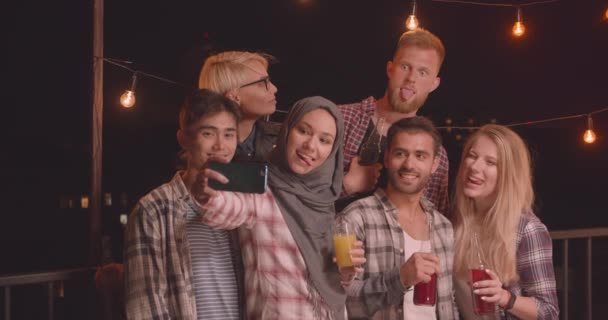 Closeup portrait of diverse multiracial group of friends taking selfies at fun party in cozy evening with fairy lights