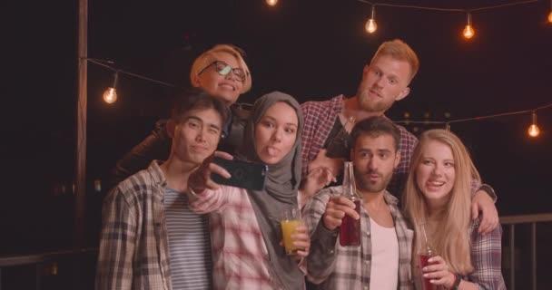 Nahaufnahme Porträt einer vielfältigen multirassischen Gruppe von Freunden, die sich umarmen und Selfies bei einer lustigen Party am gemütlichen Abend machen