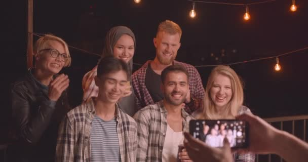 Closeup portrait of diverse multiracial group of friends being photographed on phone at fun party in cozy evening with fairy lights