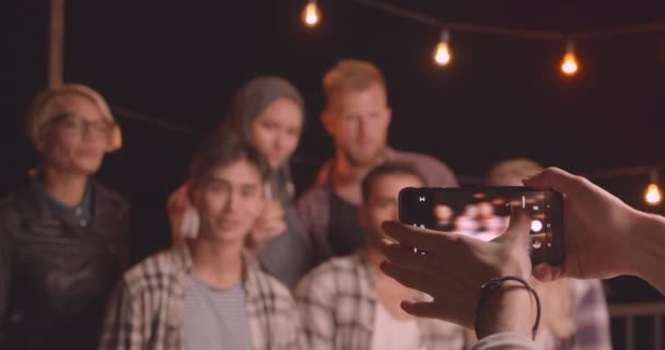 Closeup portrait of diverse multiracial group of friends being photographed on instagram camera at fun party in cozy evening