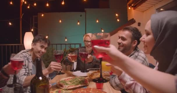 Closeup portrait of diverse multiracial group of friends celebrating drinking alcohol happily at cool party in cozy evening