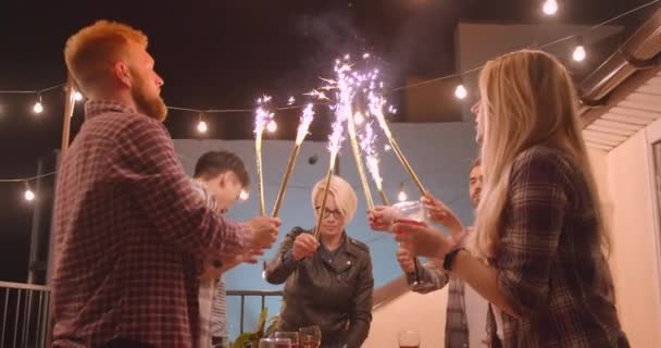 Closeup portrait of diverse multiracial cheerful group of friends celebrating happily lighting firework sticks at party in cozy evening