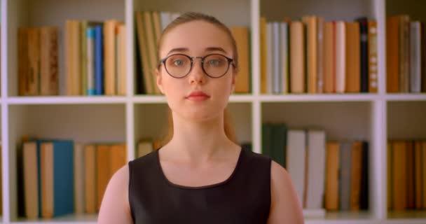 Closeup portrét mladé úspěšné ženské studentky v brýlích, které se dívají na kameru uvnitř knihovny