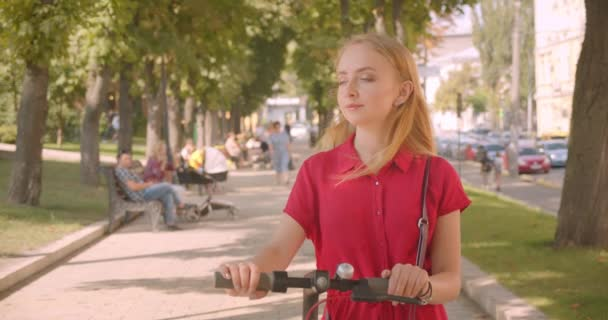 Closeup portrait of young beautiful caucasian female in red dress holding kick scooter looking at camera smiling cheerfully standing in park outdoors