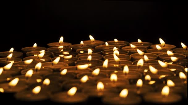Close up of a group of lit candles in the dark