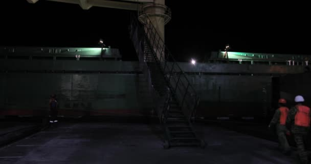 Night mooring of the cargo ship to the quay of the coal terminal. Port workers install a ladder, take mooring lines.