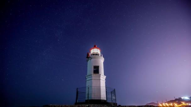 Na majáku tokarevsky ve Vladivostoku. Čas laps. Maják tokarerev na pozadí hvězdnaté oblohy a projíždějící Meteoritový proud Gemenida