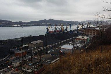 November, 2014 - Nakhodka, Russia - Coal terminal in the sea trading port of the sea city of Nakhodka. Coal collapse on the coast of a large city.