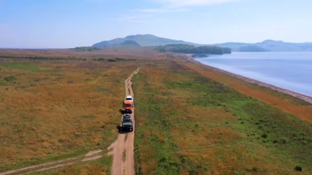 Pohled shora. Expediční auta projíždějí nekonečnými poli na pozadí modrého moře. Okouzlující krajina.