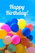 happy birthday lettering and colorful balloons in blue cloudy sky
