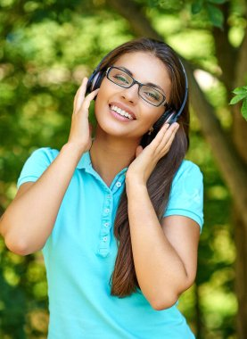 happy beautiful woman in headphones listening to music and smiling in park