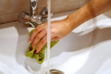 Young woman housewife washes the sink without gloves