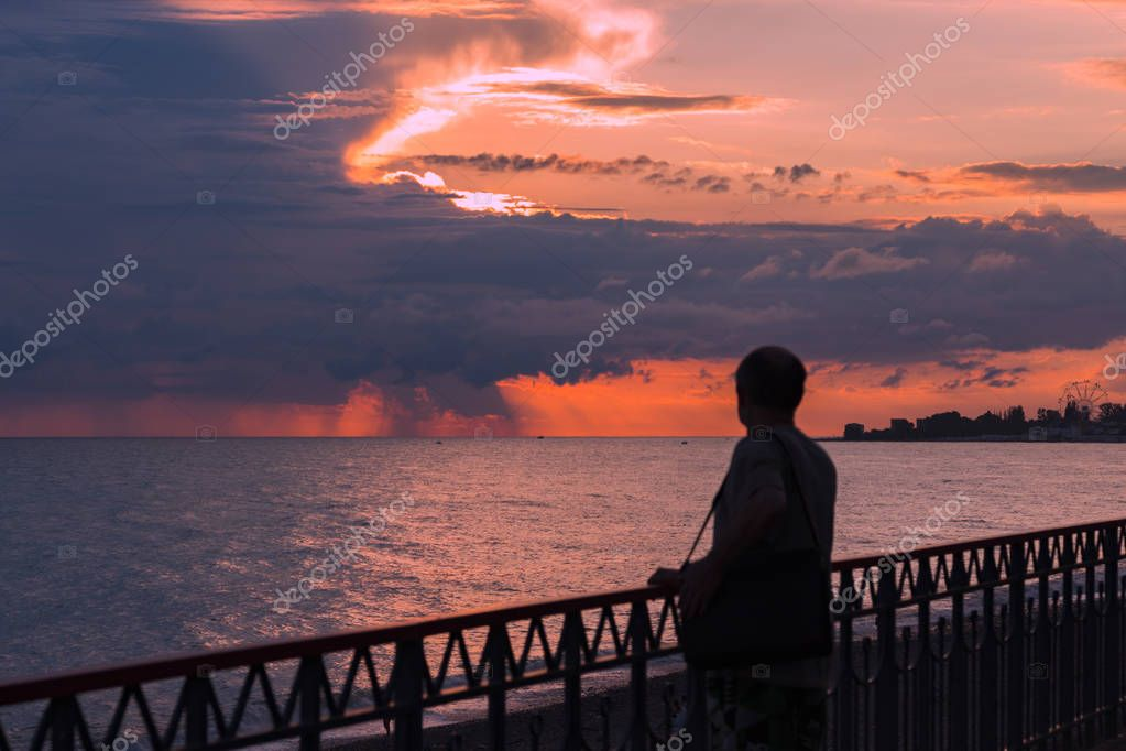 Man watching the sunset from the black sea embankment