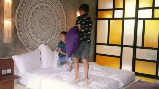 Happy kids having fun with pillows on bed. Asian brothers siblings pillow fighting at home