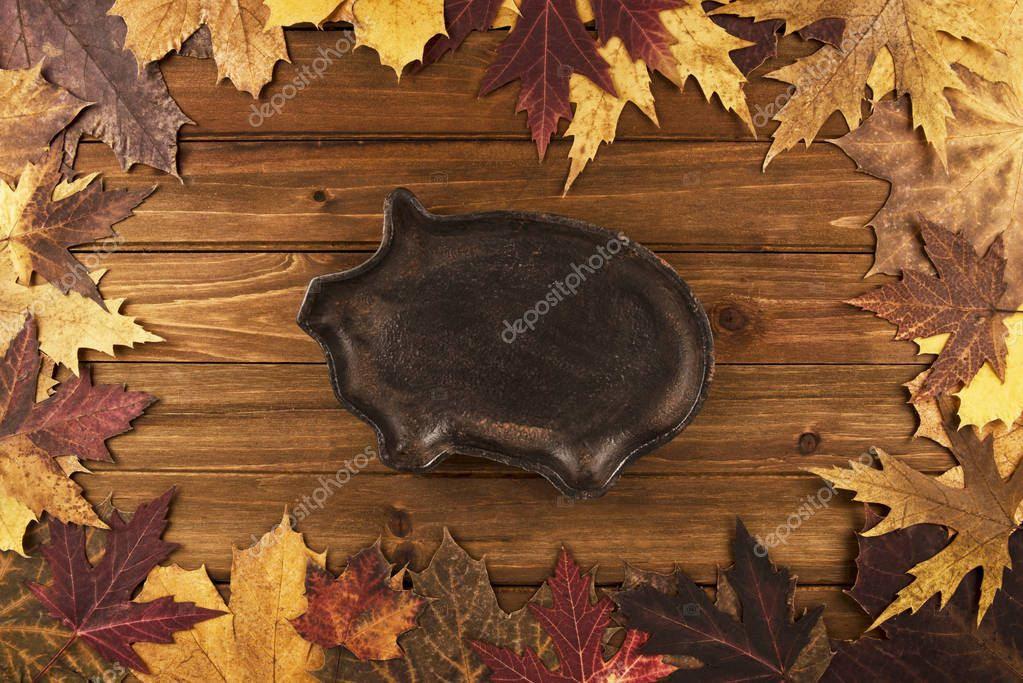 Autumn maple leaves over wooden background, pig in cast iron on center. Directly above.