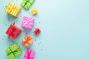Holiday flat lay with gift boxes wrapped in colorful paper and tied with bows on blue background, decorated with confetti. Birthday, Christmas and sale concept, top view.
