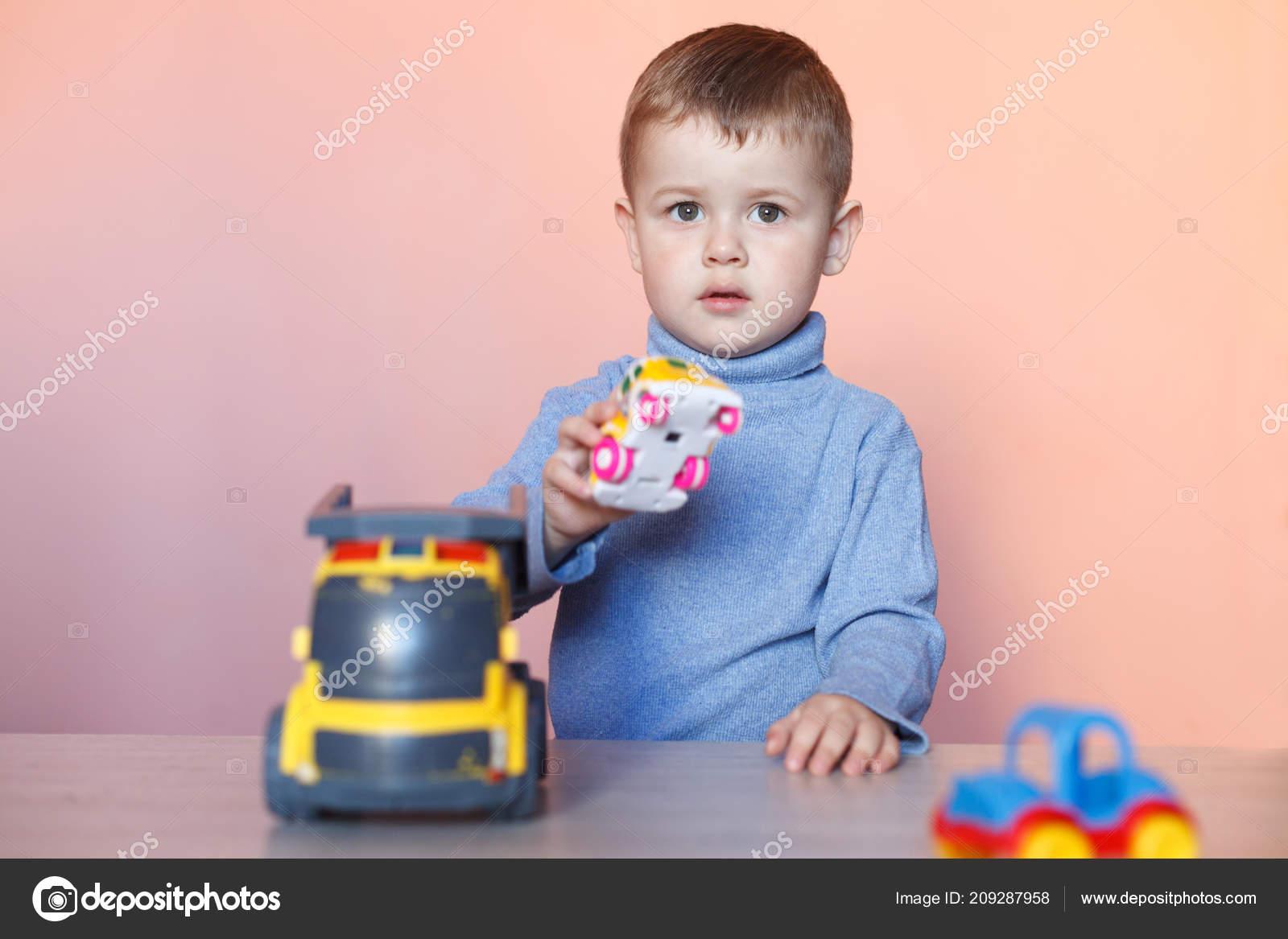 Een schattige kleine jongen spelen met model auto collectie