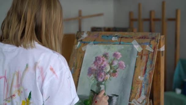 Umělec maluje obraz zátiší na stojanu.