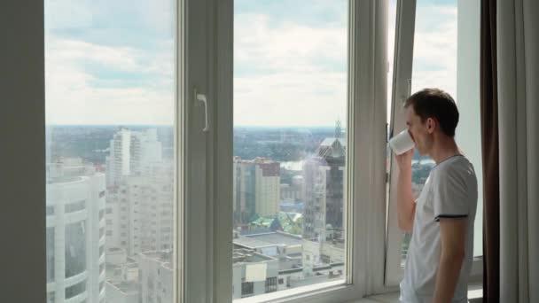 Mladý muž pije kávu nebo čaj a obdivuje pohled z okna ve městě.