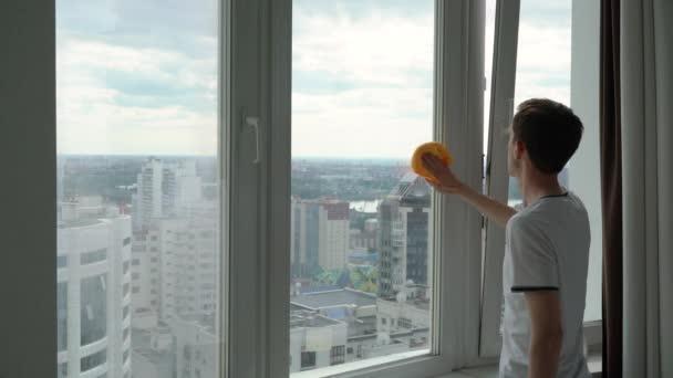 ein Mann wäscht ein Fenster mit Blick auf die Stadt.