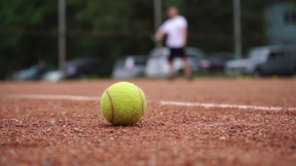 Tenisový míč ležící na dvorním hřišti na pozadí hrající tenisovou hráčku.