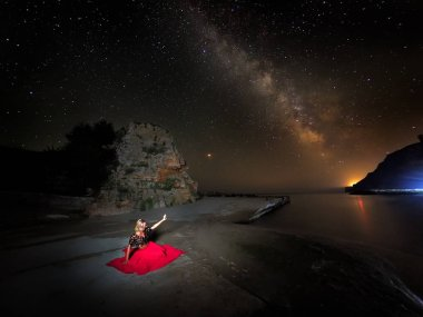 young woman and stunning vibrant Milky Way image over rocky cliffs and sea, night landscape