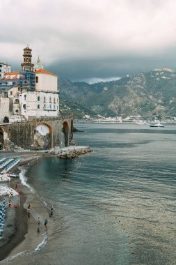 The Amalfi coast and the mountain slopes with plantations of lemons. Panoramic view of the city and nature of Italy. Evening landscapes and winding roads. Sky over the sea and rocks.
