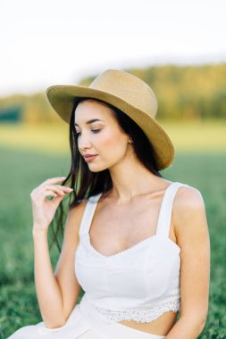 Girl walking on the field, in a hat and summer dress. Smiling and laughing, beautiful sunset in the forest and in nature. White dress and rye, sloping fields. Happy traveler, lifestyle.