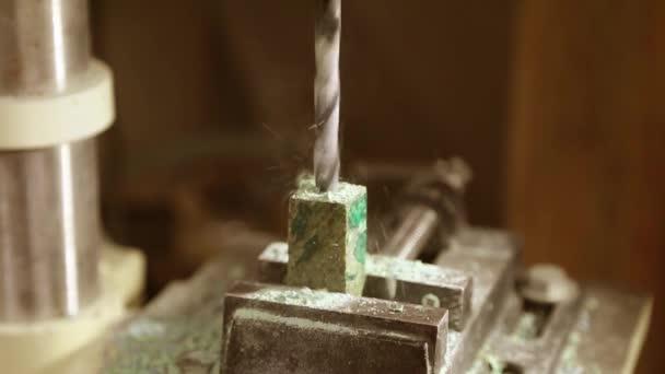Vrtání otvorů v dřevěné obrobku. Vrtací stroj zpomaleně a hobliny.