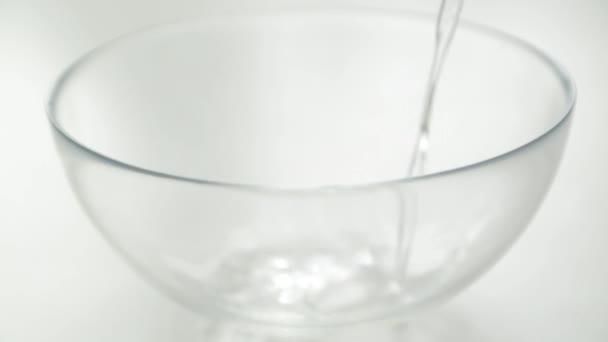 Čistou vodu nalévat do skleněné mísy. Příprava vody k vaření.
